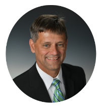 Headshot of Kentucky Farmers Bank VP/ Manager. He is smiling, wearing a suit with a green tie against a grey background.